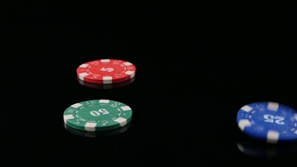 Three poker chips falling in the casino on a black background. 3