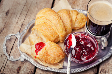 Coffee and croissants on tray on wooden background