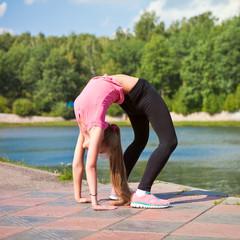 Спортивная девушка делает зарядку на природе летним днем