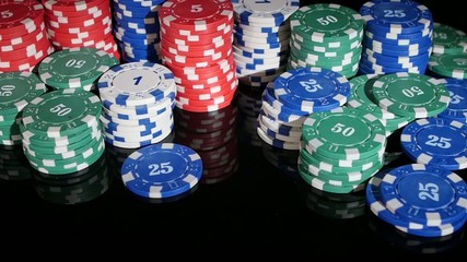 poker chips rolled into the casino on a black background. Slow
