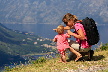 mother with baby looking at mountains on vacation