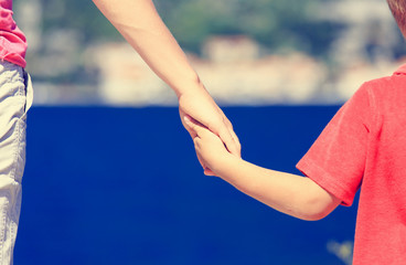 mother and kid holding hands on vacation