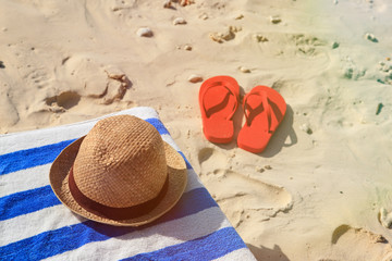 Straw hat, towel and flip flops on a sand beach