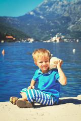 happy child listening seashell at the beach