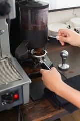 Barista grinding fresh coffee beans