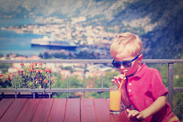 little boy drinking juice in cafe