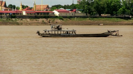 Old wood boat crossing the mekong river