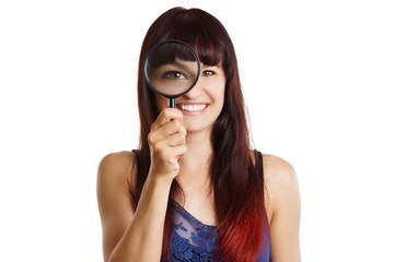 junge Frau vergrößert ihr Auge mit einer Lupe