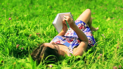Pretty girl lying on the meadow and writing in notebook