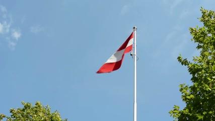 Austrian flag - green trees - blue sky - sunny