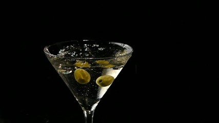 Two olives falling into a glass of martini. Slow motion