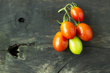 Green and red tomatoes on a  background