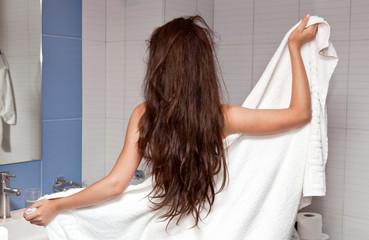 Девушка с длинными волосами стоит спиной в ванной комнате