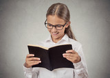 Teenage girl reading a book smiling isolated grey background
