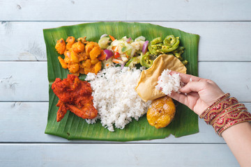 Indian woman eating banana leaf rice