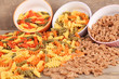 Assortment of colorful pasta in color bowls on wooden