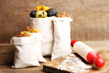 Assortment of colorful pasta in bags, rolling-pin