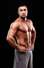 Serious muscular sportsman over black background