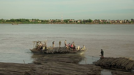 Boat loaded with bamboo canes leaving from bamboo rafts