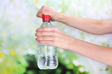 Hand holds bottle with water on background
