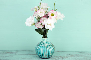Beautiful eustoma flowers in vase, on wooden background