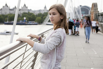 Side view portrait of pensive teenager girl standing on bridge