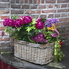 artificial dahlia in wicker basket