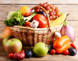 Vegetables in wicker basket on wooden background