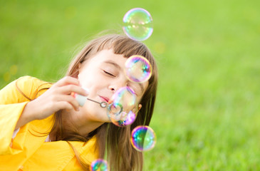 Little girl blowing soap bubbles