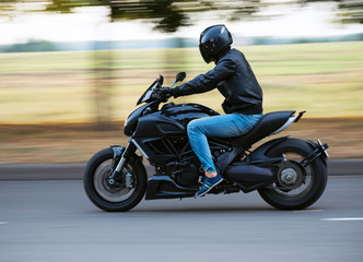 Young man riding a sport motorcycle on the road