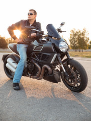 Biker man wearing a leather jacket sitting on his motorcycle out