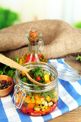 Vegetable salad in glass jar, on  napkin, on wooden background