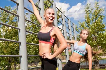 Две спортивные  девушки занимаются зарядкой на улице