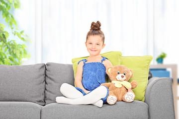 Cute little girl sitting with teddy bear on a sofa