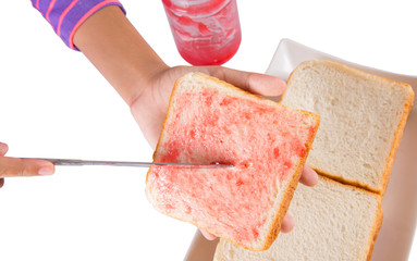 Female teen hand spreading jam on a piece of bread