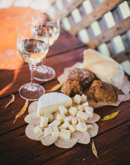 two glasses of white wine with cheese and bread on a table