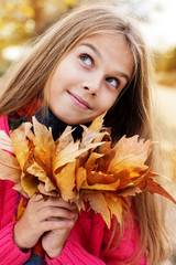 Happy child girl with fallen golden leaves