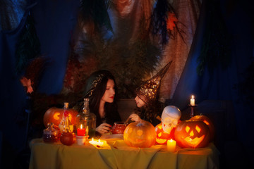 Two witch with pumpkin lantern at home