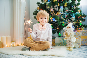 Happy boy with Bengal lights near christmas tree
