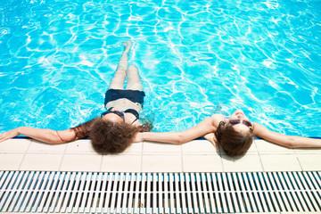 Две девушки отдыхают в бассейне