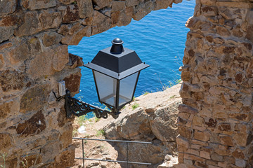 Streetlamp on the wall of fortress in Tossa de Mar.