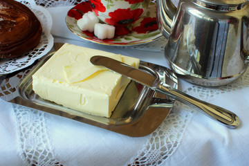 Butter in the butter-dishand and knife on a white tablecloth.