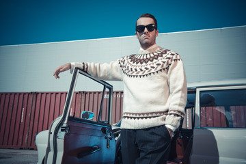 Retro fifties fashion man with woolen sweater and sunglasses sta