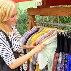 Frau beim Shopping con Kleidung