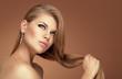 Pretty model wearing jewelery touching her long healthy hair