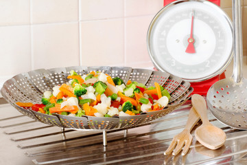 vegetable steamer with vegetables mix inside and balance