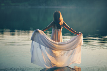 Woman with white dress in a lake at sunset