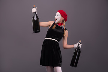 Portrait of young mime girl holding big bottles in her hands iso