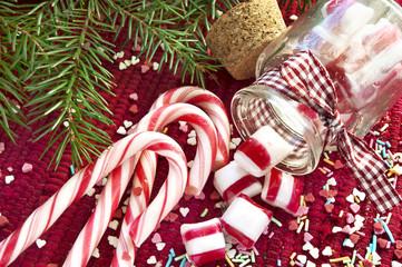 Sweet candies spilled/poured from glass jar. Green christmas fir