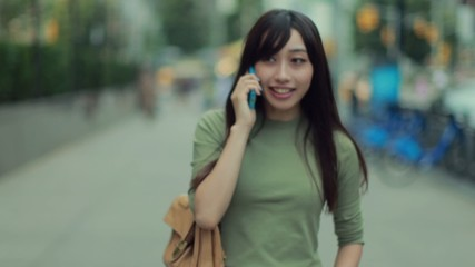 Young Asian Woman in city talking cellphone